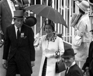 Queen Smiles Under Umbrella