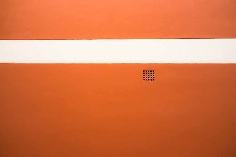 Red wall with white stripe and grate detail fine art photography