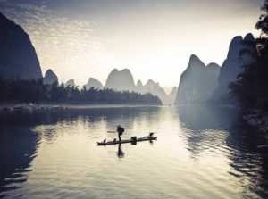 Fishermen on li river surrounded by mountains