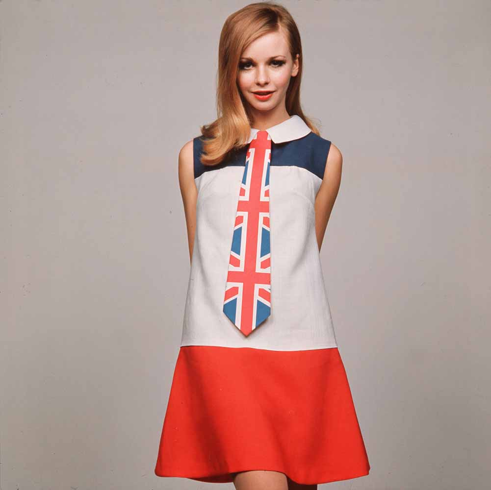 England. 1968. A model is pictured wearing a red, white and blue mini-dress with Union Jack kipper tie. fine art photography