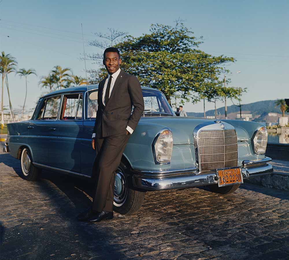 Sport. Football. pic: circa 1966. Pele, the Santos and Brazil star, wearing a smart suit and to show the trappings of his success, posing with a Mercedes car. fine art photography