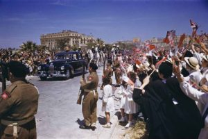 1954. Royal Tour to Malta. Queen Elizabeth II and Prince Philip, the Duke of Edinburgh, are pictured in a Land Rover acknowledging the cheers of Maltese schoolchildren at a rally on the Floriana Granaires.