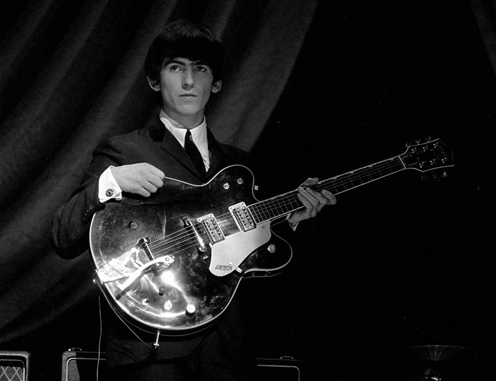 George Harrison of The Beatles pop group, holding his guitar during a rehearsal, 1963. fine art photography