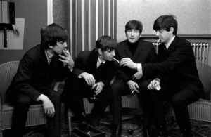Members of The Beatles pop group all wearing suits and smoking cigarettes, 1963.
