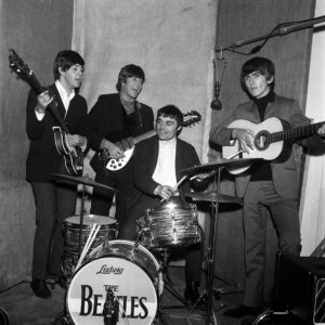 3rd June 1964. British pop group The Beatles are pictured prior to a tour of Denmark and Holland with drummer Jimmy Nicol who replaced Ringo Starr due to illness. L-R: Paul McCartney, John Lennon, Jimmy Nicol (seated on drums), and George Harrison.