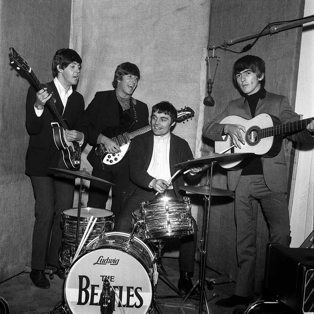 3rd June 1964. British pop group The Beatles are pictured prior to a tour of Denmark and Holland with drummer Jimmy Nicol who replaced Ringo Starr due to illness. L-R: Paul McCartney, John Lennon, Jimmy Nicol (seated on drums), and George Harrison. fine art photography