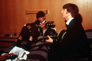 1963. The pop group The Beatles in Sweden. George Harrison and John Lennon playing their guitars as they rehearse in their Stockholm hotel room.