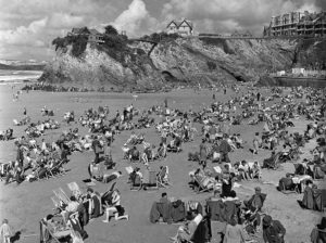 1949. Newquay, Cornwall, England. Crowds of people enjoy the weather as they sunbathe on the beach.
