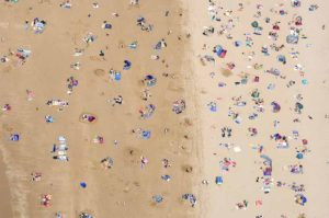 Swimmers and surfers on beach, aerial view