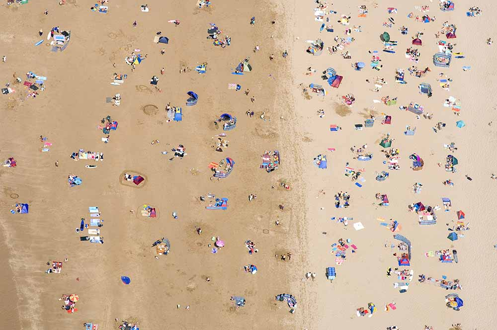 Swimmers and surfers on beach, aerial view fine art photography