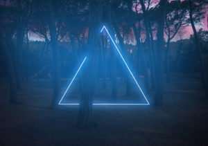 Blue neon triangle light between pine trees with futuristic visual effect.