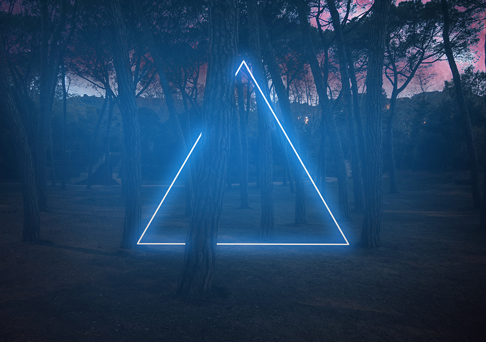 Blue neon triangle light between pine trees with futuristic visual effect. fine art photography