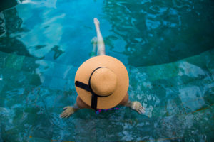 Beautiful portrait of a traveler girl in swimming pool with hat taken from above with nice composition with legs during travel vacations in Indonesia.