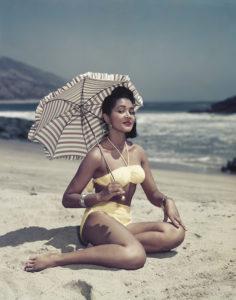 Woman on Beach Holding Umbrella